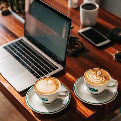 Kaffeetassen mit Laptop und Smartphone auf Tisch